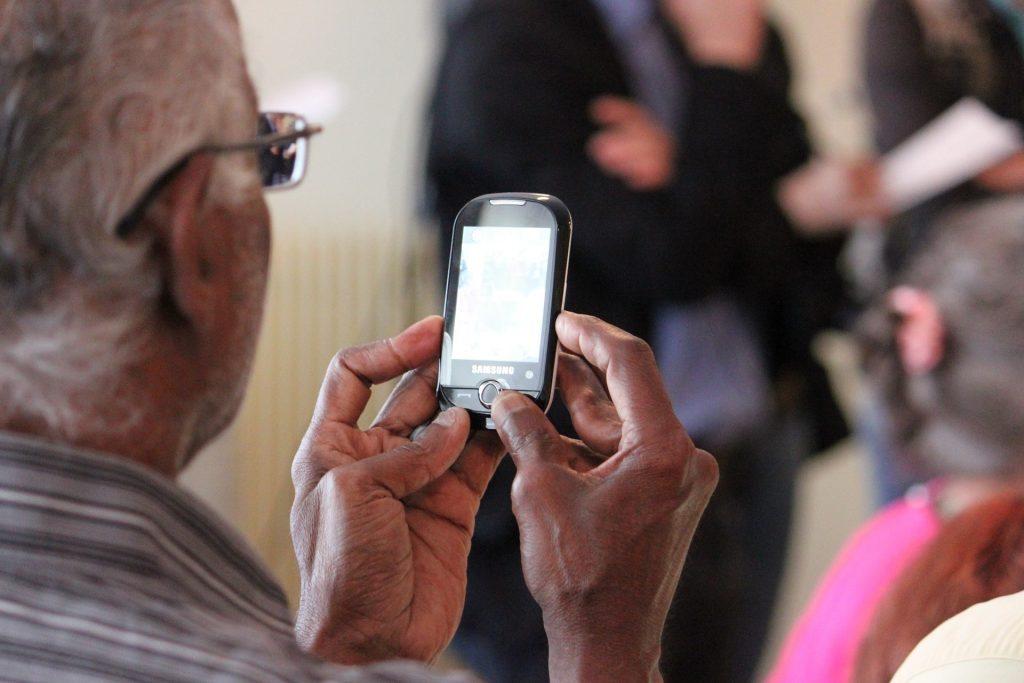 Senior hält Smartphone in der Hand
